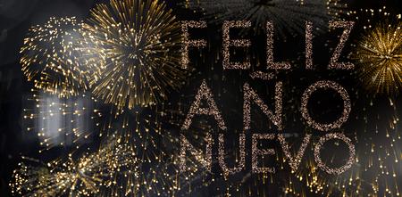 nuevo: Glittering feliz ano nuevo against colourful fireworks exploding on black background