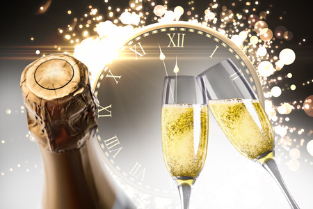 against the clock: Champagne glasses clinking against clock counting down to midnight