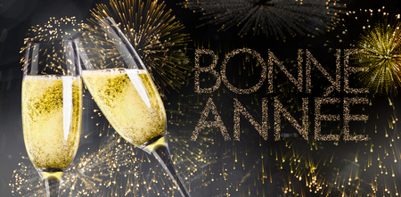 bonne: Champagne glasses clinking against glittering bonne annee Stock Photo