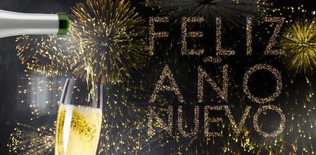 ano: Champagne pouring against glittering feliz ano nuevo Stock Photo