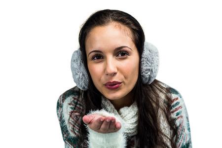 Earmuffs: Smiling woman with earmuffs blowing kiss on white screen Stock Photo