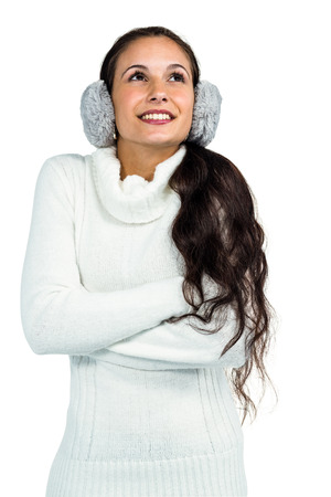 crossing arms: Smiling woman with earmuffs crossing arms and looking up on white screen Stock Photo