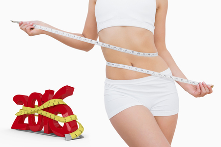 woman measuring waist: Slim woman measuring waist with tape measure against white background with vignette Stock Photo