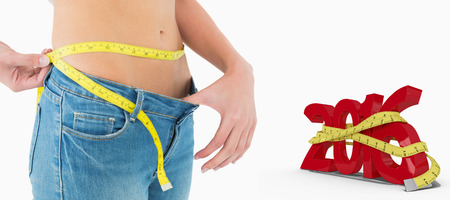 woman measuring waist: Mid section of woman measuring waist in a big sized jeans against white background with vignette