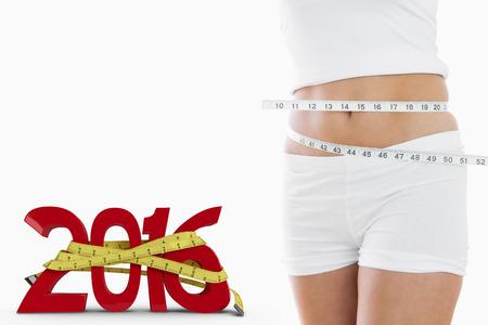 woman measuring waist: Closeup midsection of woman measuring waist against white background with vignette