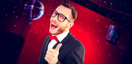 cheesy grin: Geeky hipster pointing at camera against pretty brunette dancing and smiling