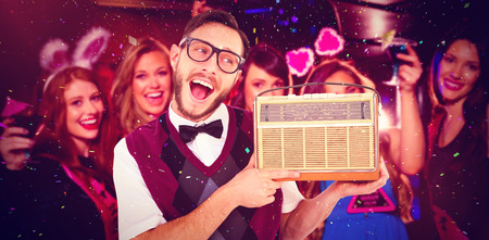 together with long tie: Geeky hipster holding a retro radio against pretty friends on a hen night