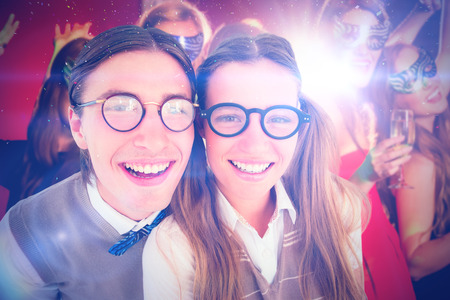 hedonistic: Geeky hipsters smiling at camera  against friends in masquerade masks drinking champagne Stock Photo