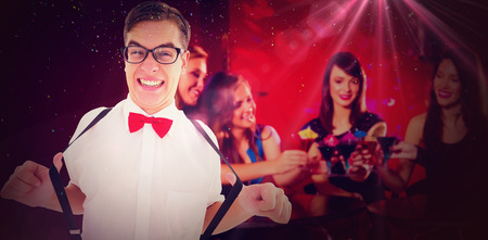 Geeky hipster pulling his suspenders against pretty friends drinking cocktails together Imagens