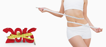 measuring waist: Slim woman measuring waist with tape measure against white background with vignette Stock Photo