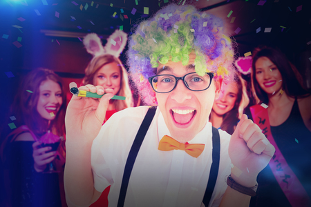 together with long tie: Geeky hipster wearing a rainbow wig holding party horn against pretty friends on a hen night