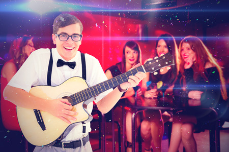 together with long tie: Geeky hipster playing guitar and singing against pretty friends drinking cocktails together