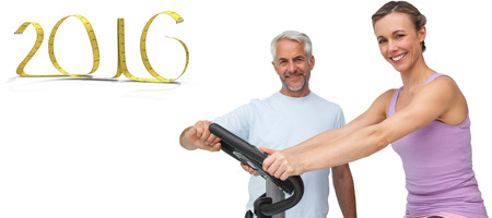 stationary bike: Portrait of a happy woman on stationary bike with trainer against white background with vignette