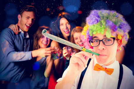 hedonistic: Geeky hipster wearing a rainbow wig blowing party horn against happy friends drinking shots smiling at camera Stock Photo