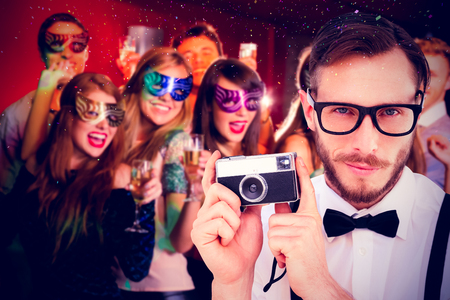 geeky: Geeky hipster holding a retro camera against friends in masquerade masks drinking champagne