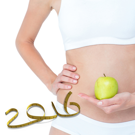 young adult woman: Woman holding an apple in front of her belly  against white background with vignette Stock Photo