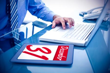 december: Businessman using his laptop  against december 31st