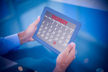 using tablet: Businessman using his tablet  against month of december on calendar Stock Photo
