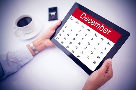using tablet: Man using tablet pc against month of december on calendar Stock Photo