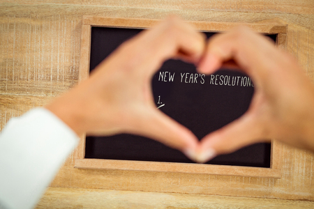 new years resolution: New years resolution list against hands making heart shape