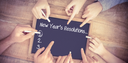 new rules: New years resolution list against hands writing on chalkboard Stock Photo
