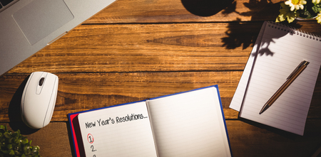 books on a wooden surface: New years resolution list against overhead view of an desk