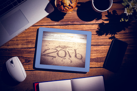 books on a wooden surface: View of a desk against 2016 on sand at beach