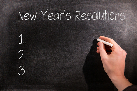 new rules: New years resolution list against man drawing on chalkboard