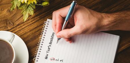 Neue Jahre Auflösung Liste gegen beschnittene Handschrift von Kaffeetasse auf dem Tisch im Buch Standard-Bild