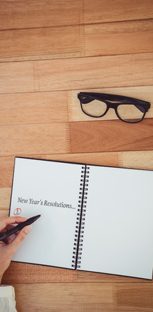 new years resolution: New years resolution list against cropped image of woman writing on notepad