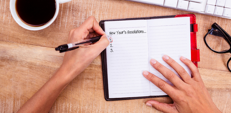 new rules: New years resolution list against businesswoman writing on diary on desk Stock Photo