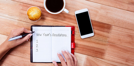 new rules: New years resolution list against overhead of feminine hands writing on agenda Stock Photo