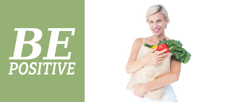 woman holding bag: Attractive woman holding bag of vegetables  against green vignette Stock Photo