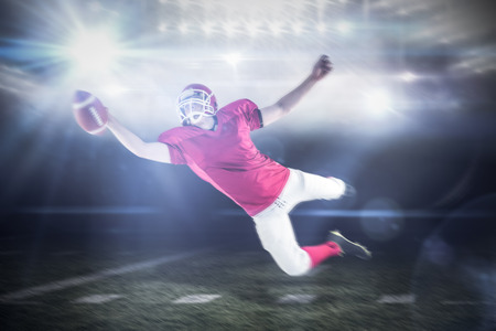 touchdown: American football player scoring a touchdown against sports pitch Stock Photo
