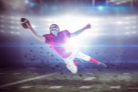 uniforme de futbol: Jugador de fútbol americano de anotar un touchdown contra estadio de fútbol americano Foto de archivo