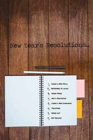 workbook: New year resolution list against white background against close up view of a workbook