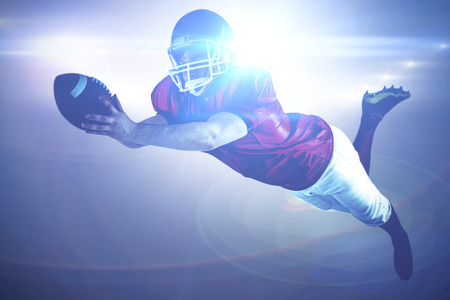 scoring: American football player scoring a touchdown against spotlights Stock Photo