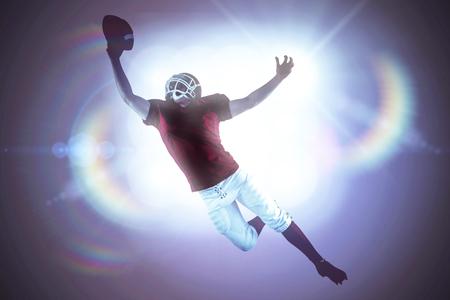 scoring: American football player scoring a touchdown against spotlights Stock Photo