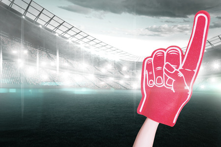foam hand: American football player holding supporter foam hand against sports arena Stock Photo