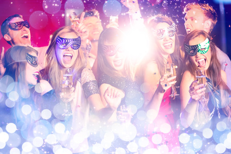 hedonistic: Glowing background against friends in masquerade masks drinking champagne