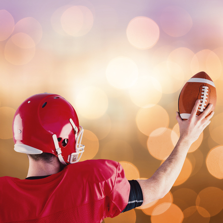 holding up: Rear view of american football player holding up football against blue glowing background