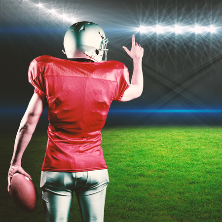 winning pitch: Rear view of American football player pointing while holding ball against rugby stadium