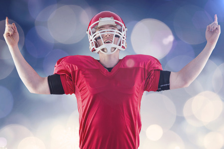 triumphing: American football player triumphing  against glowing christmas background