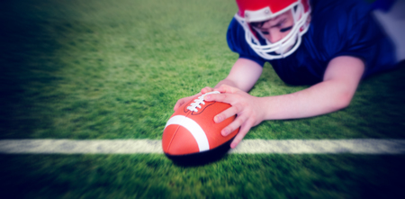 scoring: American football player scoring a touchdown against rugby pitch