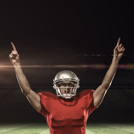 winning pitch: American football player with arms raised standing against rugby pitch