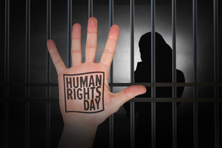 behind bars: Hand with fingers spread out against human rights Stock Photo