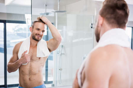 personal grooming: Handsome man looking in mirror at home in the bathroom