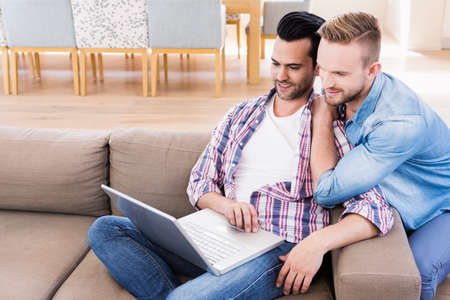 couple on couch: Gay couple relaxing on the couch using laptop at home in the living room