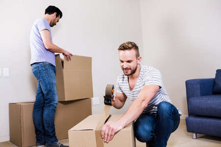 sealing tape: Gay couple moving into new home at home in the living room