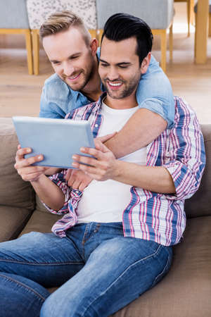 couple on couch: Gay couple relaxing on the couch using tablet at home in the living room